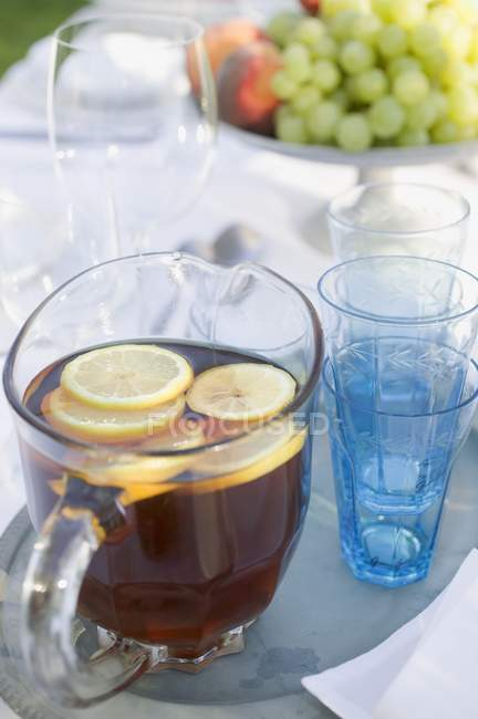 Iced tea with slices of lemon in jug — Stock Photo