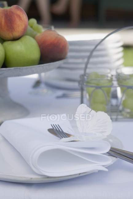 Nahaufnahme gedeckter Tisch mit Obst am Ständer, Besteck und Geschirr — Stockfoto