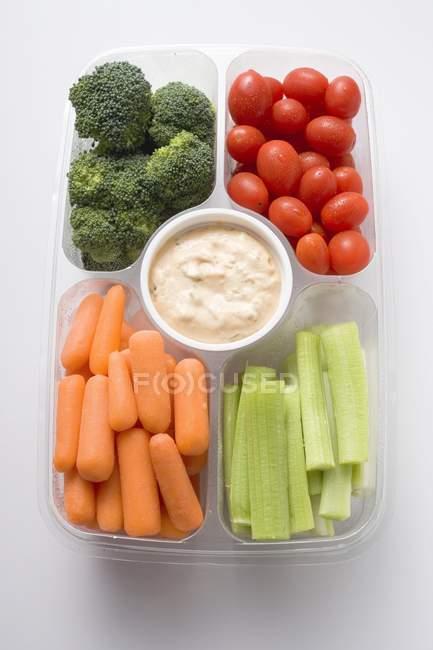 Verduras surtidas con inmersión en bandeja de plástico sobre superficie blanca - foto de stock