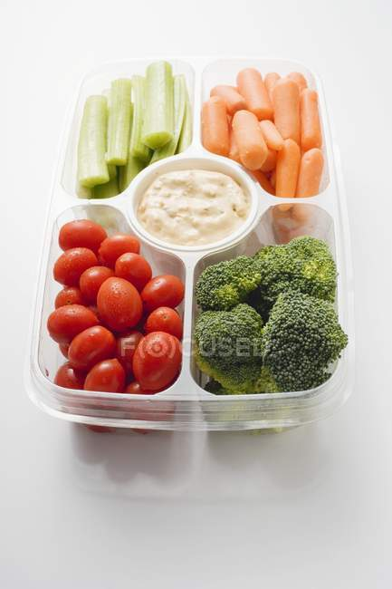 Assorted vegetables with dip in plastic tray on white surface — Stock Photo