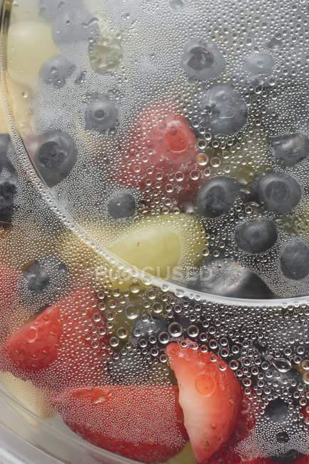 Closeup view of fruit salad in wet plastic container — Stock Photo