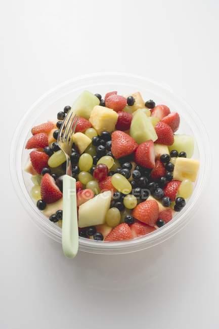 Вид крупным планом фруктового салата в пластиковой миске с вилкой — стоковое фото