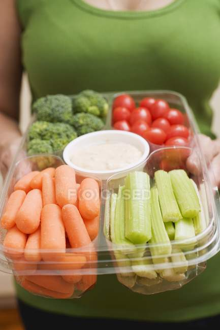Cropped view of woman holding plastic tray of vegetables and dip — Stock Photo