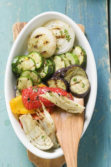 Vista superior de verduras a la plancha con una espátula de madera en plato ovalado - foto de stock