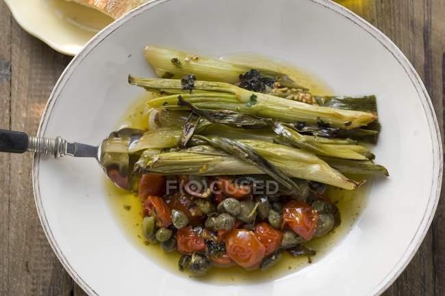 Puerros con tomate y alcaparras - foto de stock