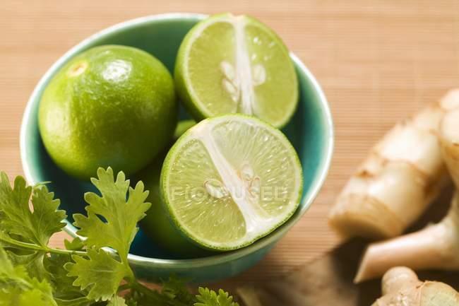 Limes em tigela com coentro — Fotografia de Stock