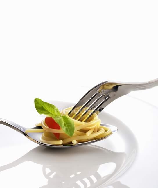 Spaghetti mit Tomaten und Basilikum auf Löffel — Stockfoto