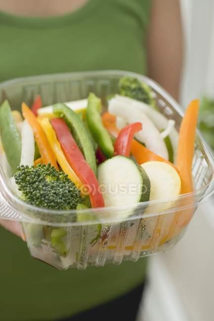 Mulher segurando recipiente de plástico de legumes fatiados em mãos, parte central — Fotografia de Stock