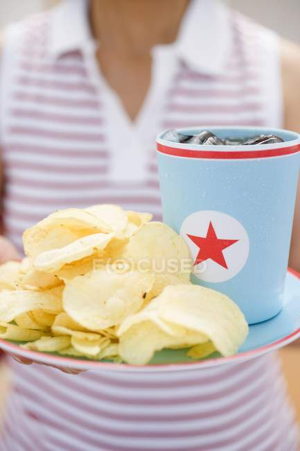Woman holding potato crisps and beaker of cola on plate — Stock Photo