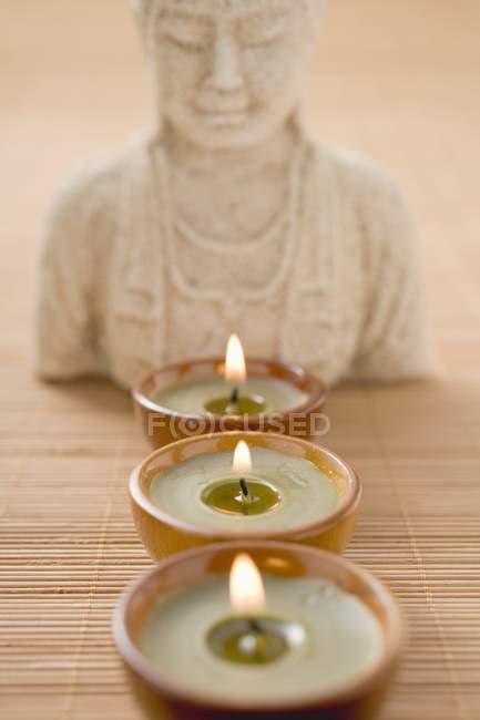 Tealights em frente à estátua de Buddha — Fotografia de Stock
