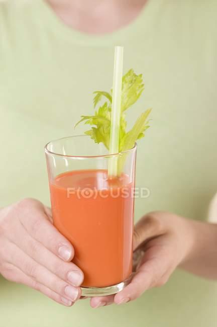 Donna che tiene vetro di succo di carota — Foto stock