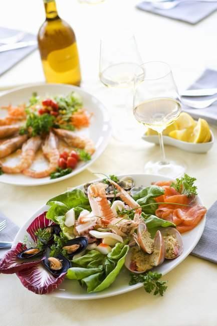 Повышенный вид разнообразных закусок из морепродуктов и белого вина — стоковое фото