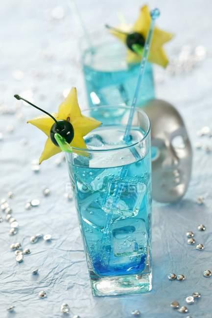 Крупный план коктейлей Blue Lagoon с кусочками звездных фруктов и вишней — стоковое фото