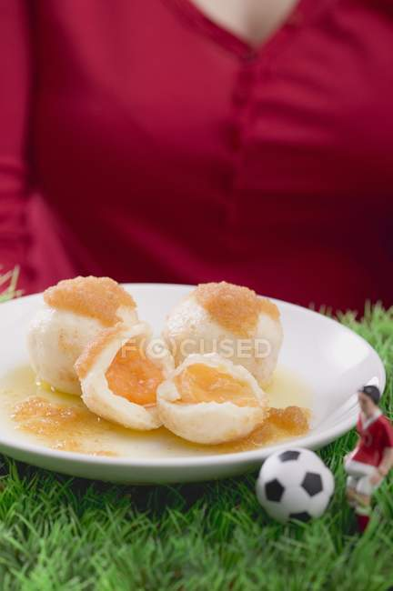 Woman serving apricot dumplings with football figure and football in hands, midsection — Stock Photo