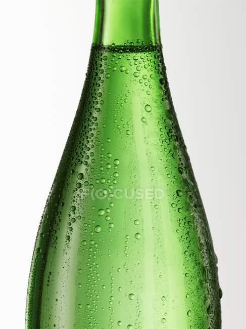 Vista de perto da garrafa de vidro verde com condensação — Fotografia de Stock