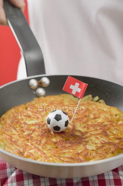Mão, segurando a frigideira com rsti, futebol de brinquedo & bandeira Suíça — Fotografia de Stock