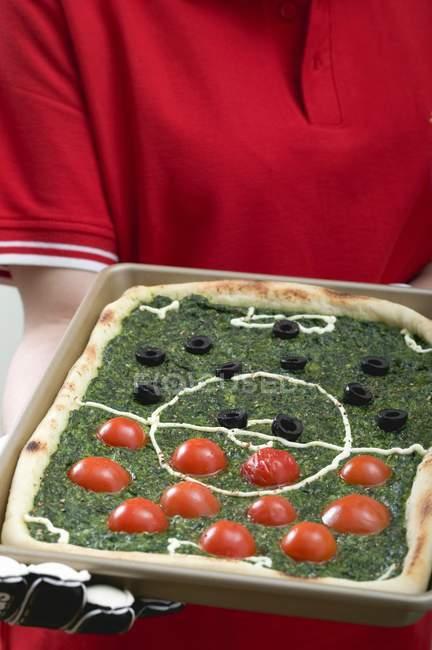 Footballer holding pizza — Stock Photo