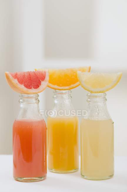 Tres zumos de frutas en botellas - foto de stock