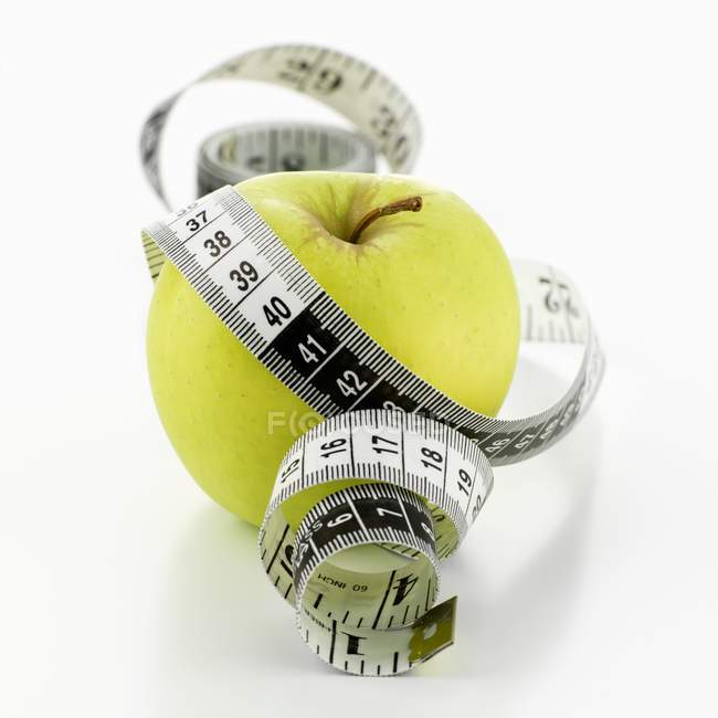 Green apple with tape measure — Stock Photo