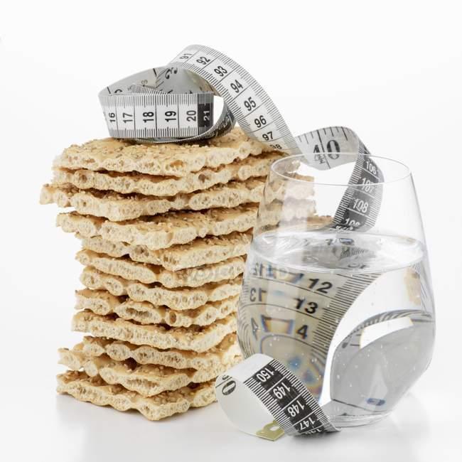 Pan crujiente y vaso de agua - foto de stock