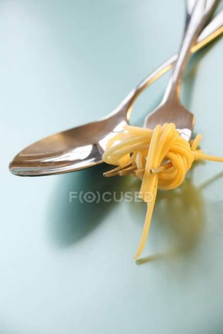 Cuchara y tenedor con espaguetis - foto de stock
