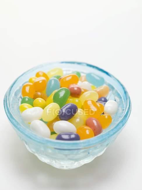 Желейные бобы в голубой стеклянной тарелке — стоковое фото