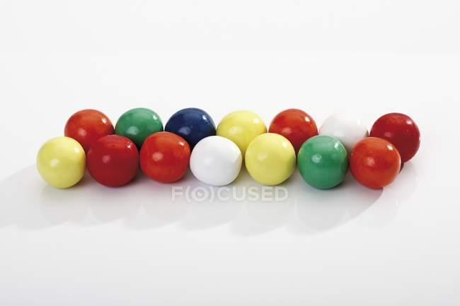 Вид крупным планом цветных шариков жвачки подряд — стоковое фото