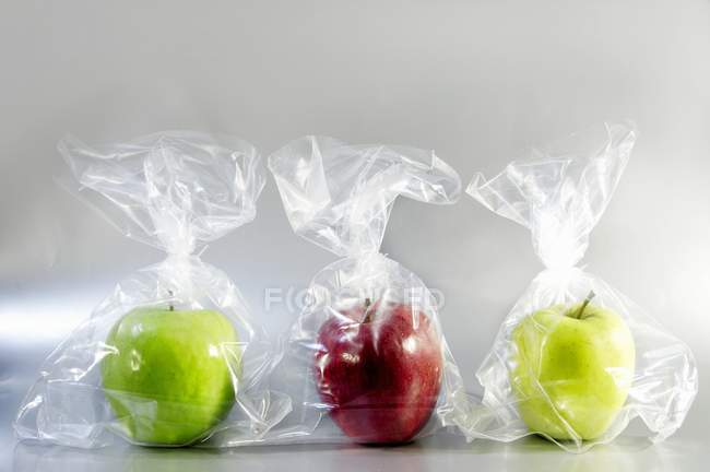 Three apples in plastic bags — Stock Photo