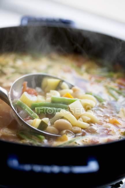 Cozinhar sopa de legumes em panela com concha — Fotografia de Stock