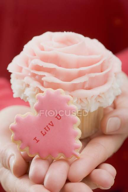 Hands holding cupcake and biscuit — Stock Photo