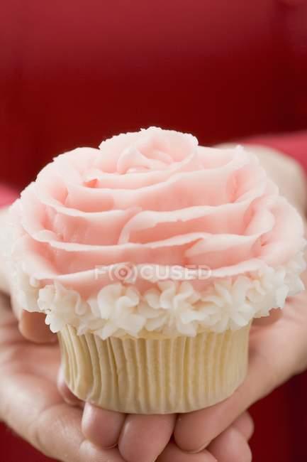 Weibliche Hand hält Cupcake — Stockfoto
