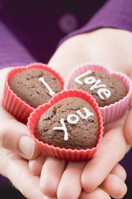 Primo piano vista ritagliata delle mani che tengono panini al cioccolato per San Valentino — Foto stock