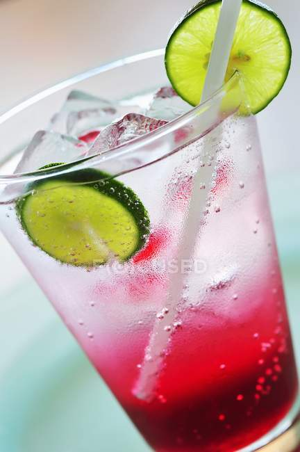 Closeup view of raspberry soda with ice cubes and lime slices in glass — Stock Photo