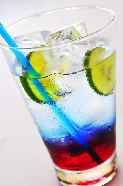 Closeup view of colored soft drink with ice cubes and lime slices — Stock Photo