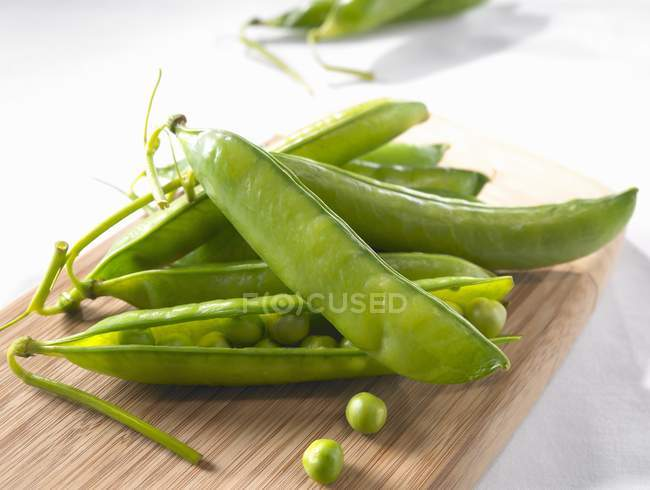 Fresh green pods and peas — Stock Photo