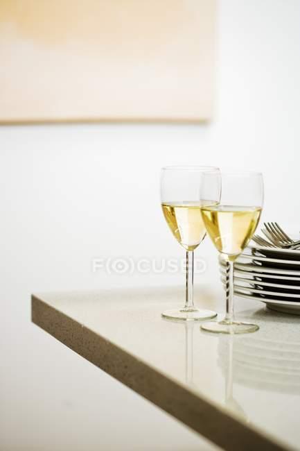 Стакана белого вина, рядом куча пластин — стоковое фото