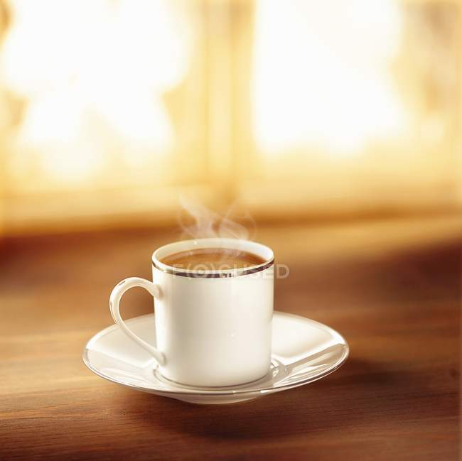 Coffee in silver-rimmed cup — Stock Photo