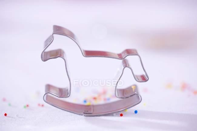 Крупным планом вид лошадки печенья резец с цветными брызгает на белой поверхности — стоковое фото