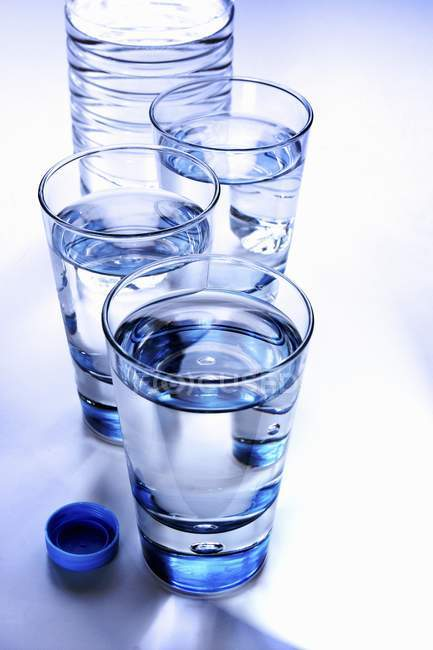Glasses of clear water and plastic bottle — Stock Photo