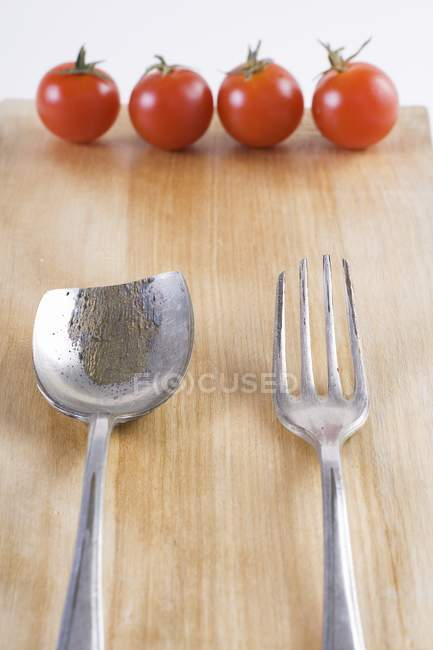 Old cutlery and four cherry tomatoes on wooden surface — Stock Photo