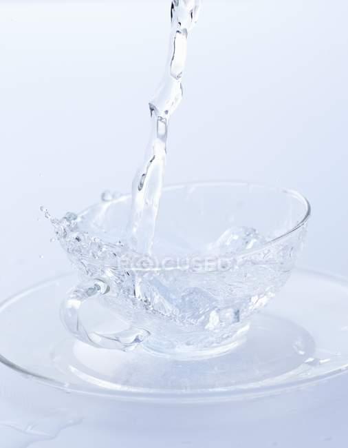 Despejar água em copo de vidro — Fotografia de Stock