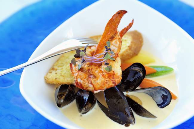 Closeup view of lobster and mussel stew with sprouts — Stock Photo