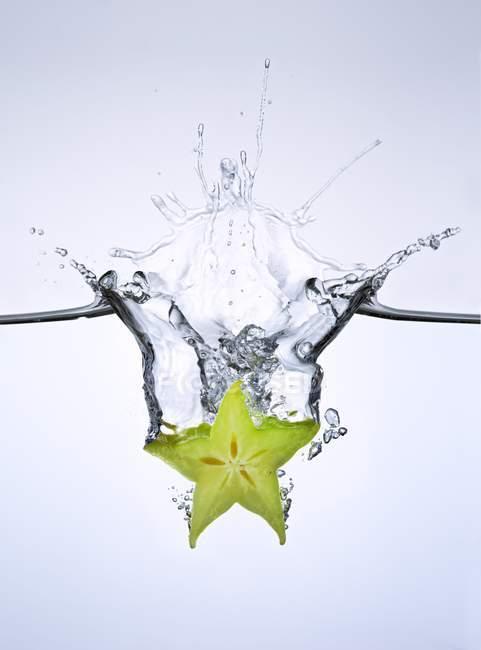Rebanada de carambola cayendo al agua - foto de stock