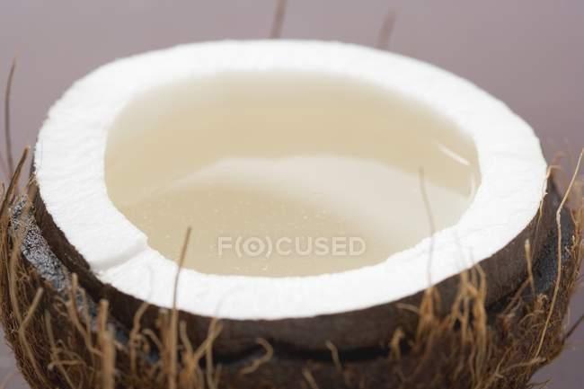 Половина из кокоса с водой — стоковое фото
