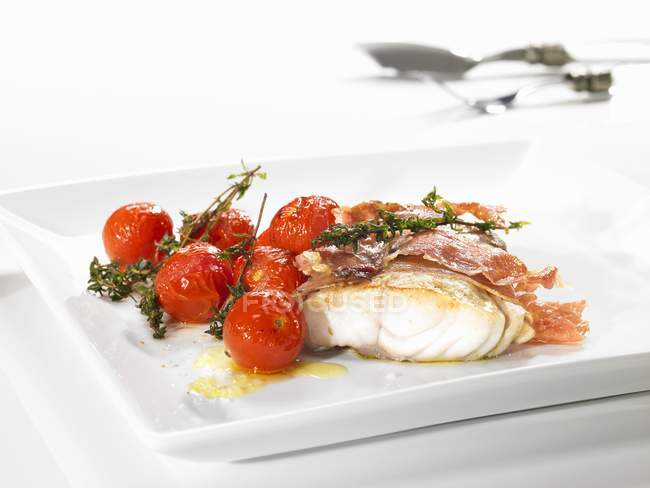 Coal-fish wrapped in ham and cherry tomatoes — Stock Photo