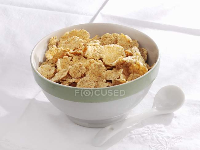 Bowl of cornflakes with spoon — Stock Photo