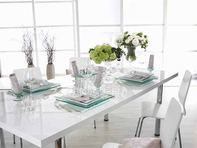 Daytime view of white laid table with flowers — Stock Photo