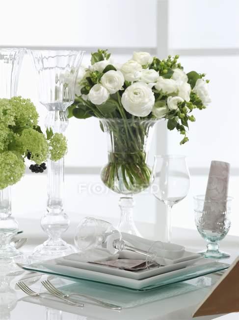 Um arranjo de flor festiva e botões de ouro brancos na tabela descontraída — Fotografia de Stock