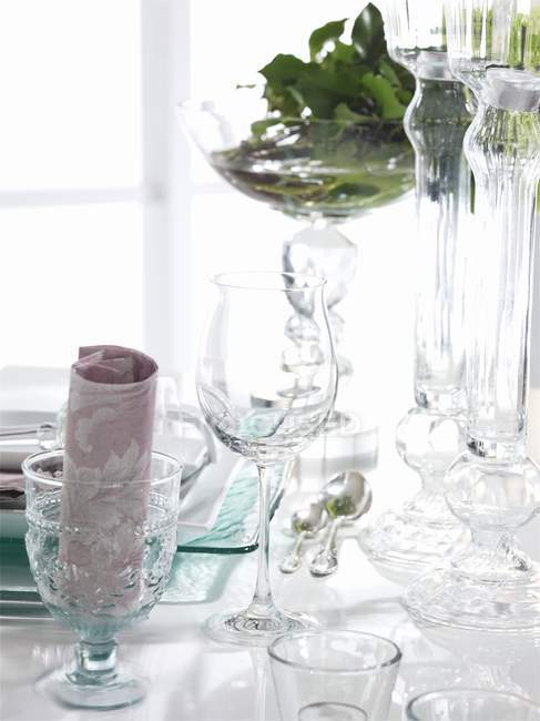 A table laid with different glasses and watered herbs — Stock Photo