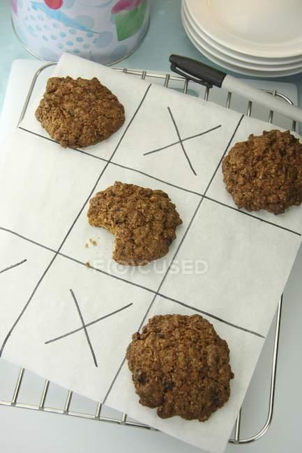 Vista elevada de galletas de avena en trozo de papel con sustantivos y cruces juego - foto de stock